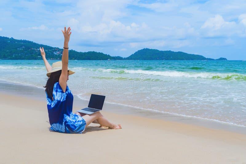 Mujer asiática feliz que usa un ordenador portátil del ordenador en la playa durante vacaciones de los días de fiesta del viaje a foto de archivo libre de regalías