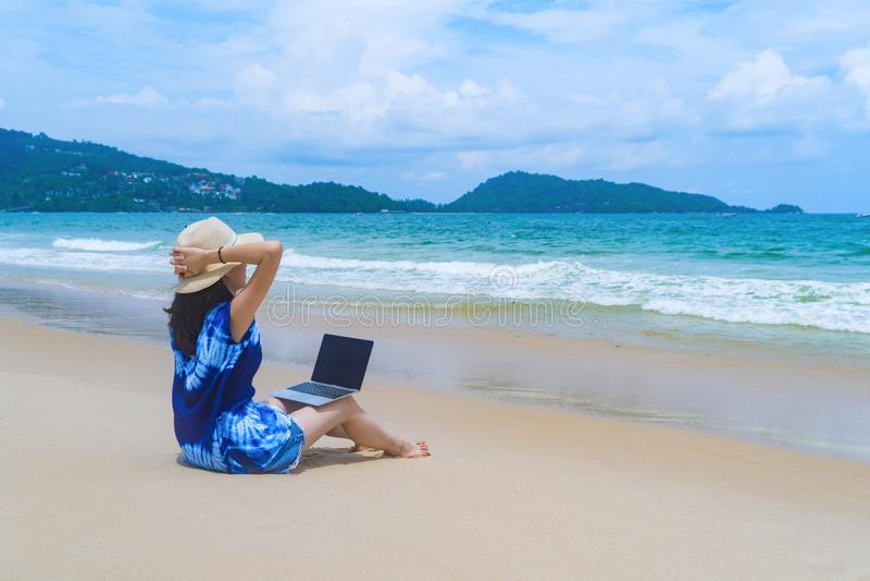 Mujer asiática feliz que usa un ordenador portátil del ordenador en la playa durante vacaciones de los días de fiesta del viaje a imágenes de archivo libres de regalías