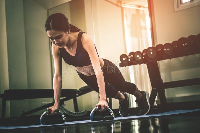 Mujer asiática fuerte que hace un tablón en un gimnasio de la aptitud fotos de archivo libres de regalías