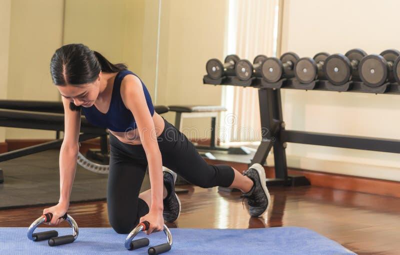 Mujer asiática fuerte que hace un tablón en un gimnasio de la aptitud fotografía de archivo