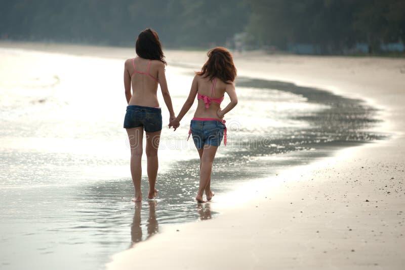 Mujer asiática gemela que recorre en la playa. imágenes de archivo libres de regalías