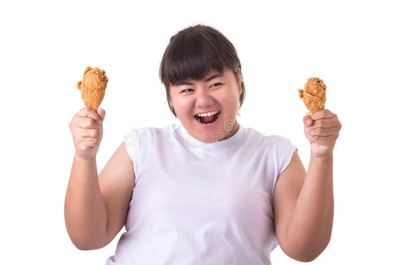 Mujer asiática gorda que sostiene y que come el pollo frito aislado en whi fotos de archivo