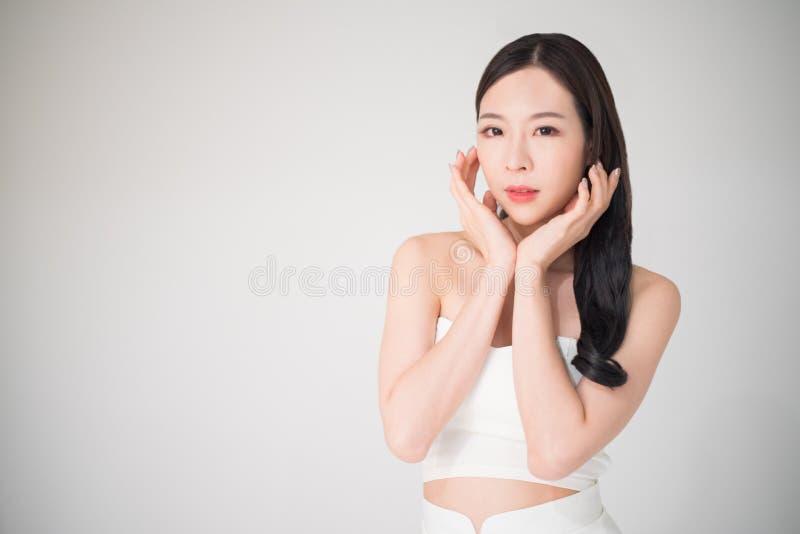 Mujer asiática hermosa con cuidado de piel o el aislador facial del concepto del cuidado imágenes de archivo libres de regalías