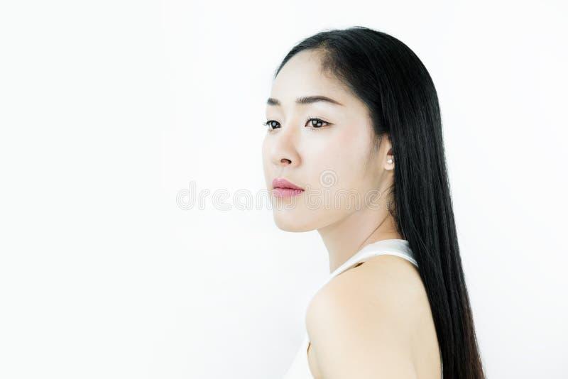 Mujer asiática hermosa con el pelo negro, con la piel sana, en el fondo blanco foto de archivo libre de regalías