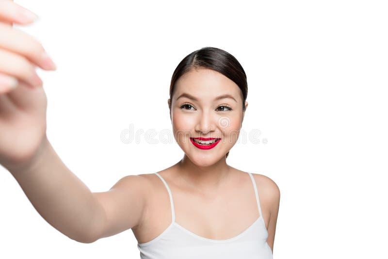 Mujer asiática hermosa con maquillaje retro con los labios rojos que toman el sel fotos de archivo libres de regalías