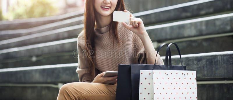 Mujer asiática hermosa con panieres y una tarjeta imagen de archivo