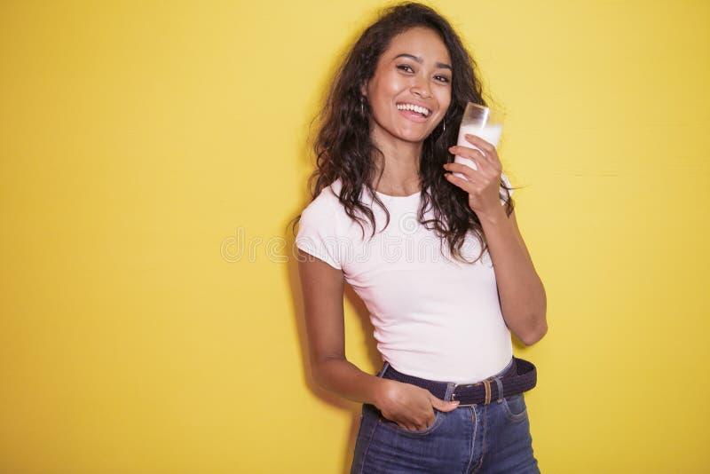 Mujer asiática hermosa con un vidrio de leche fresca foto de archivo