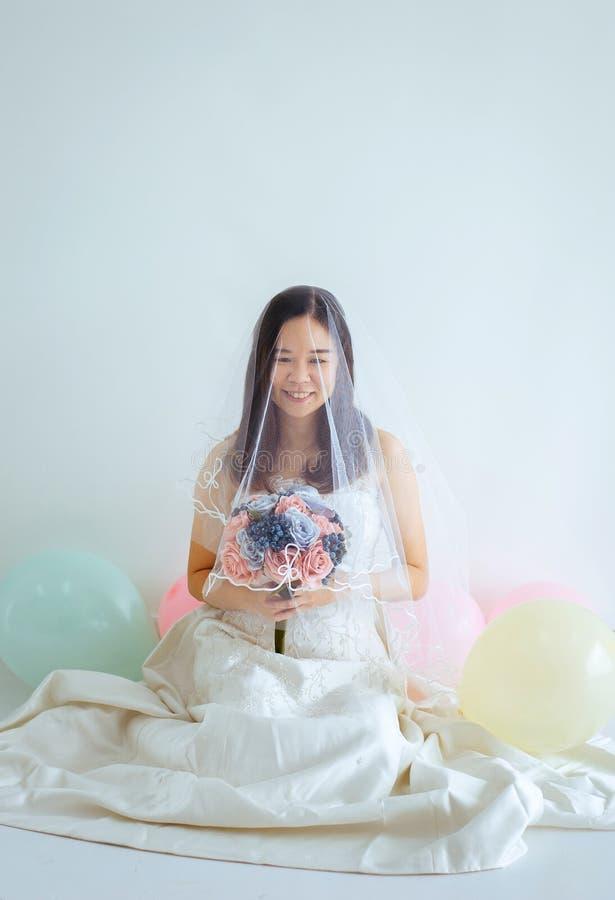 Mujer asiática hermosa de la novia en las manos blancas del vestido que sostienen la flor con la sensación feliz y divertida imagen de archivo