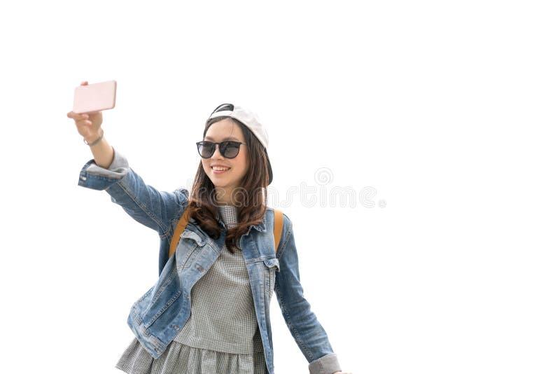 Mujer asiática hermosa del viajero que toma el selfie con el espacio de la copia, aislante en el fondo blanco, concepto del viaje imagenes de archivo