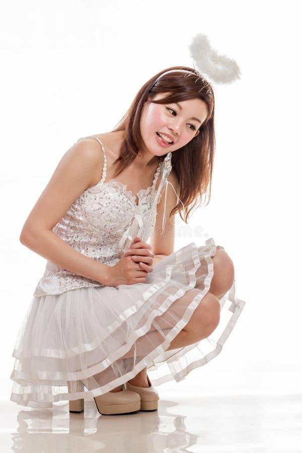 Mujer asiática hermosa en Angel Costume, mirada que se sienta abajo imagenes de archivo