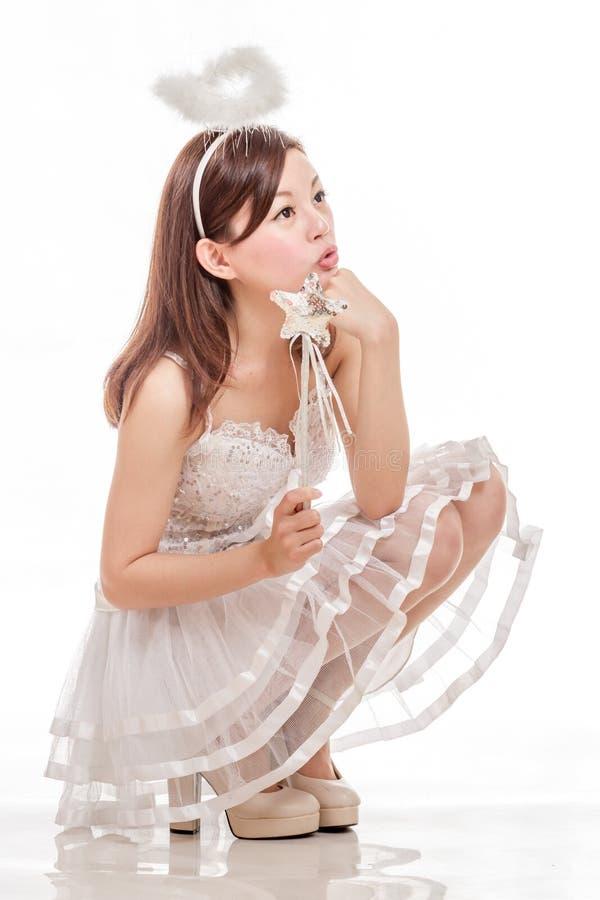 Mujer asiática hermosa en Angel Costume, mirada que se sienta para arriba fotografía de archivo libre de regalías