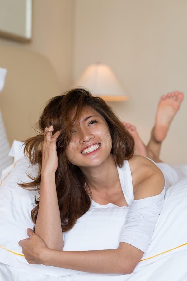 Mujer asiática hermosa en el dormitorio acogedor fotos de archivo