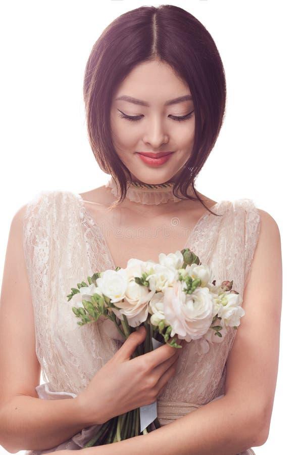 Mujer asiática hermosa en el vestido blanco con el ramo de flores en manos imagenes de archivo