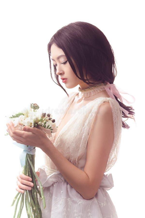 Mujer asiática hermosa en el vestido blanco con el ramo de flores en manos imagen de archivo libre de regalías