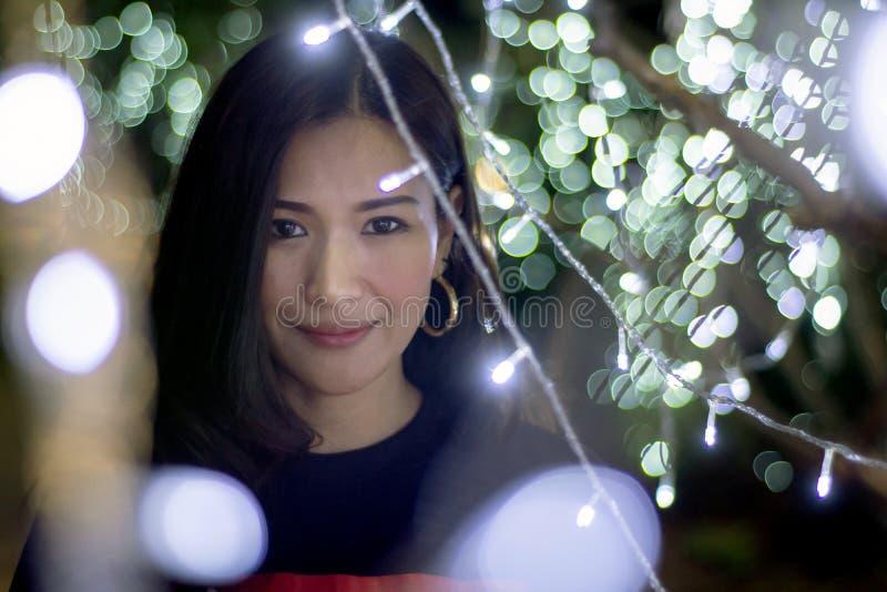 Mujer asiática hermosa en un fondo con las luces del color del bokeh, efecto luminoso borroso imágenes de archivo libres de regalías