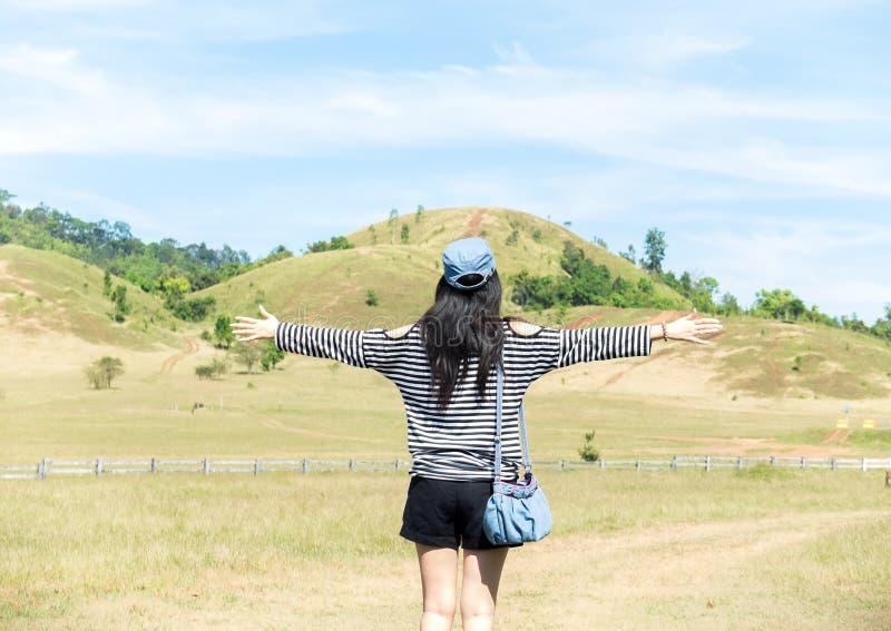 Mujer asiática hermosa feliz con el sombrero y bolso listo para comenzar vacaciones con la montaña del paisaje en fondo imagenes de archivo