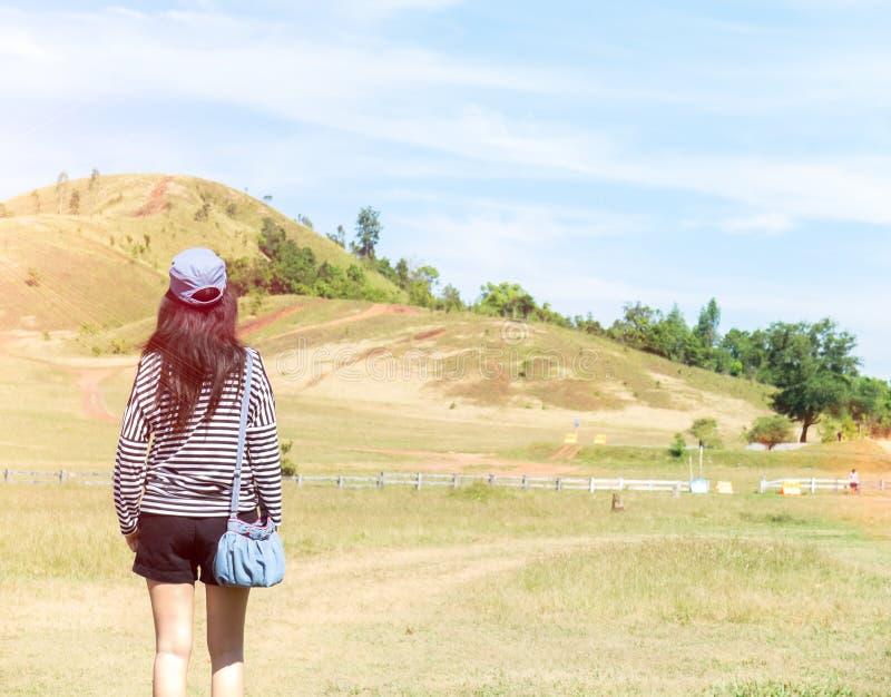 Mujer asiática hermosa feliz con el sombrero y bolso listo para comenzar vacaciones en la esquina con la montaña del paisaje en f imágenes de archivo libres de regalías