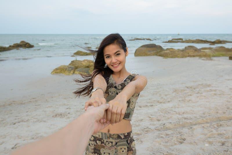 Mujer asiática hermosa feliz joven que sonríe mientras que se sostiene con bot imágenes de archivo libres de regalías