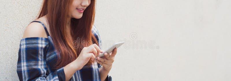 Mujer asiática hermosa feliz que usa un smartphone en fondo gris imágenes del estilo del efecto del vintage Bandera panorámica fotos de archivo libres de regalías