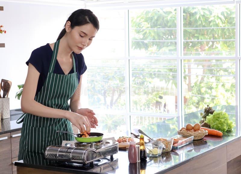 Mujer asiática hermosa joven con los cocineros verdes del delantal de la raya en la cacerola imágenes de archivo libres de regalías