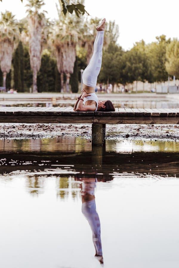 mujer asiática hermosa joven que hace yoga en un parque El sentarse en el puente con la reflexión en el lago del agua Yoga y sano fotografía de archivo