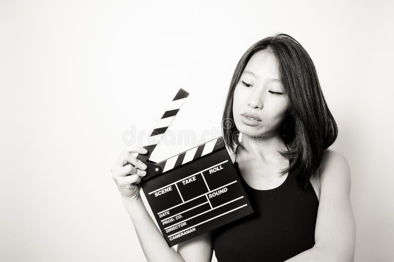 Mujer asiática hermosa joven que mira negro del clapperboard y w foto de archivo libre de regalías