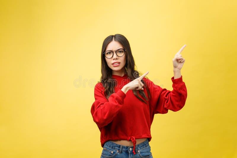 Mujer asiática hermosa joven que señala al copyspace, en fondo amarillo fotografía de archivo