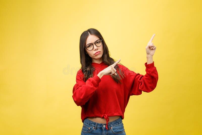 Mujer asiática hermosa joven que señala al copyspace, en fondo amarillo foto de archivo
