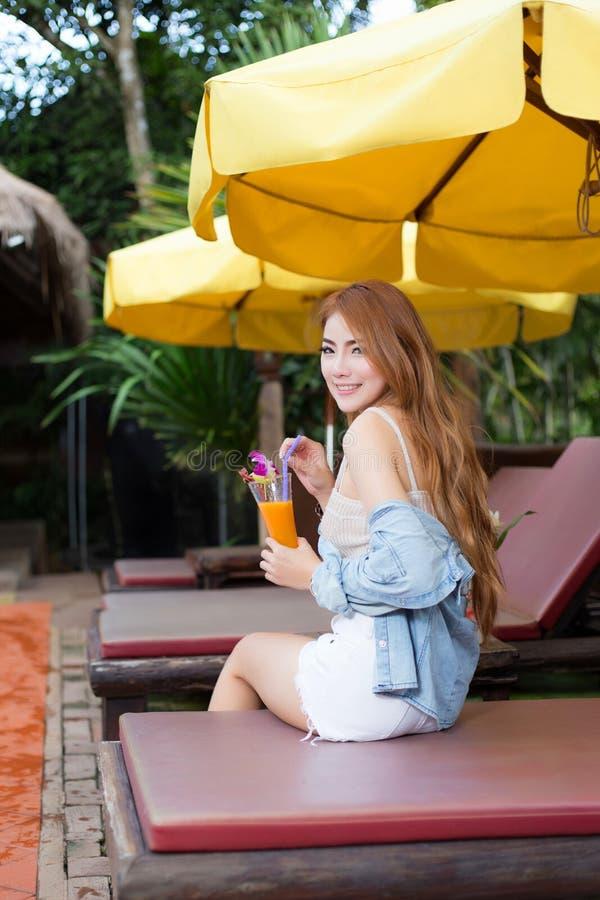 Mujer asiática hermosa joven que se relaja en centro turístico foto de archivo