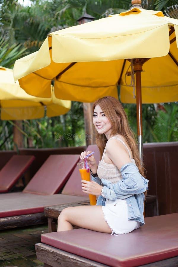 Mujer asiática hermosa joven que se relaja en centro turístico fotos de archivo libres de regalías