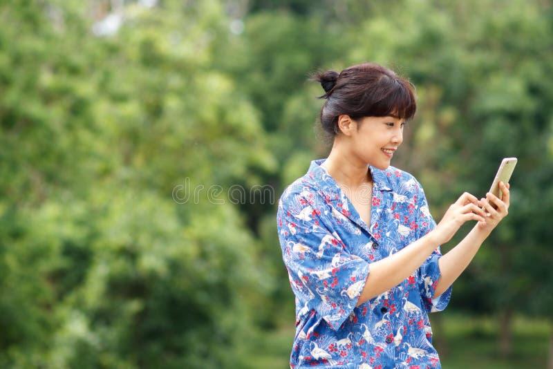 Mujer asiática hermosa joven que sonríe mientras que lee su smartphone fotografía de archivo libre de regalías