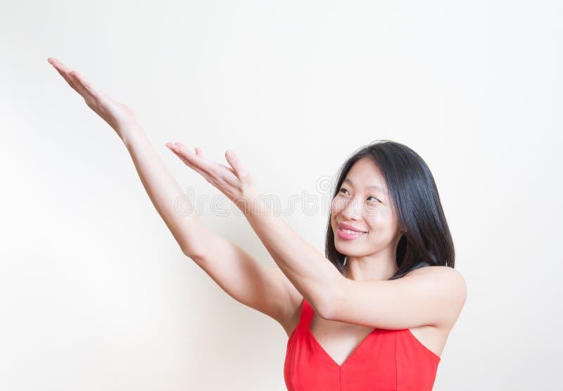 Mujer asiática hermosa joven que sonríe señalando el backgroun blanco foto de archivo libre de regalías