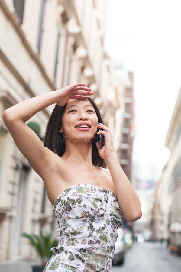 Mujer asiática hermosa joven que sonríe usando el teléfono móvil urbano hacia fuera imágenes de archivo libres de regalías