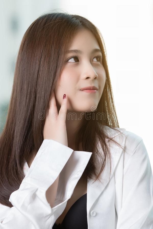 Mujer asiática hermosa por la ventana imagenes de archivo