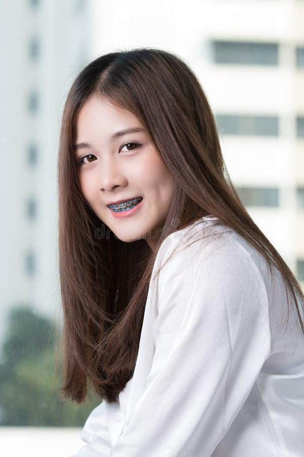 Mujer asiática hermosa por la ventana foto de archivo