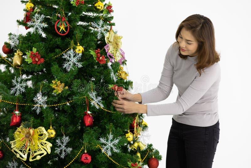 Mujer asiática hermosa que adorna su árbol de navidad de Hugh con lo foto de archivo