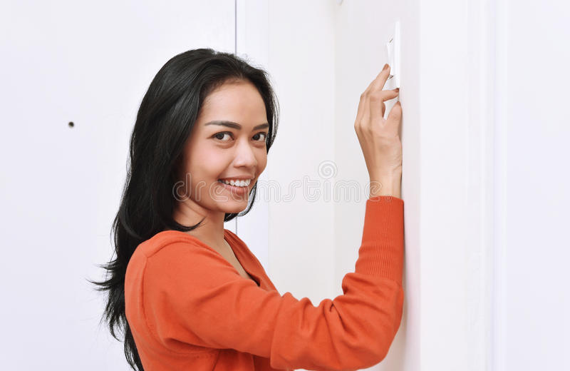 Mujer asiática hermosa que apaga la luz con el interruptor de la pared imágenes de archivo libres de regalías