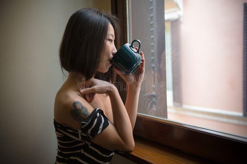 Mujer asiática hermosa que bebe con la taza azul que mira la ventana imagen de archivo libre de regalías