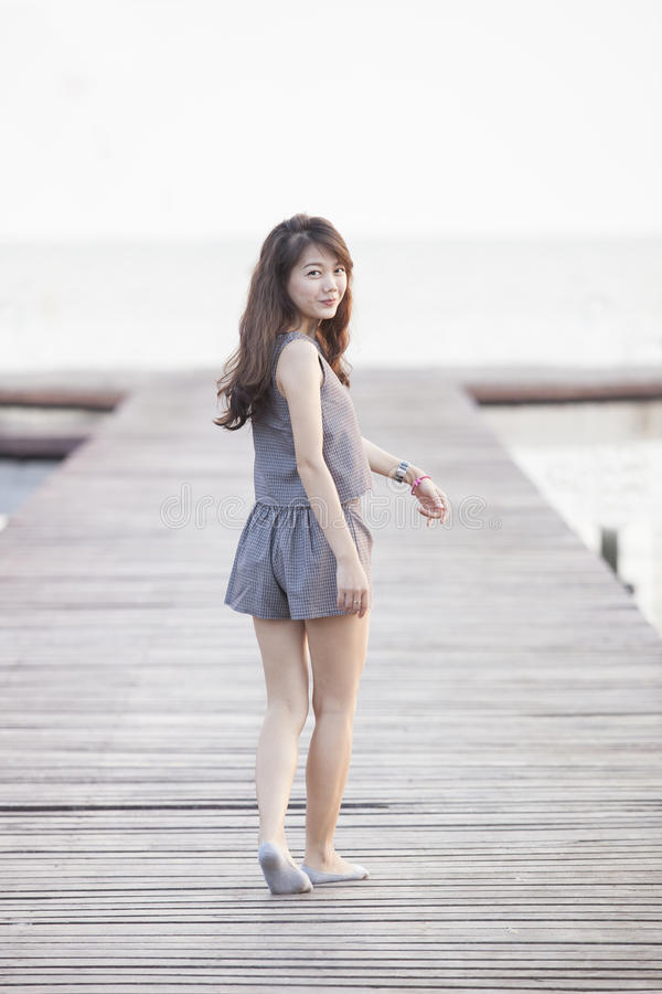 Mujer asiática hermosa que camina en el embarcadero de madera con la emoción relajante y que sonríe al uso de la cámara para la ed foto de archivo libre de regalías