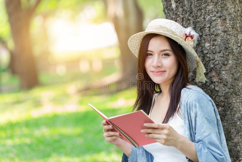 Mujer asiática hermosa que lee el libro rosado en el parque fotos de archivo libres de regalías