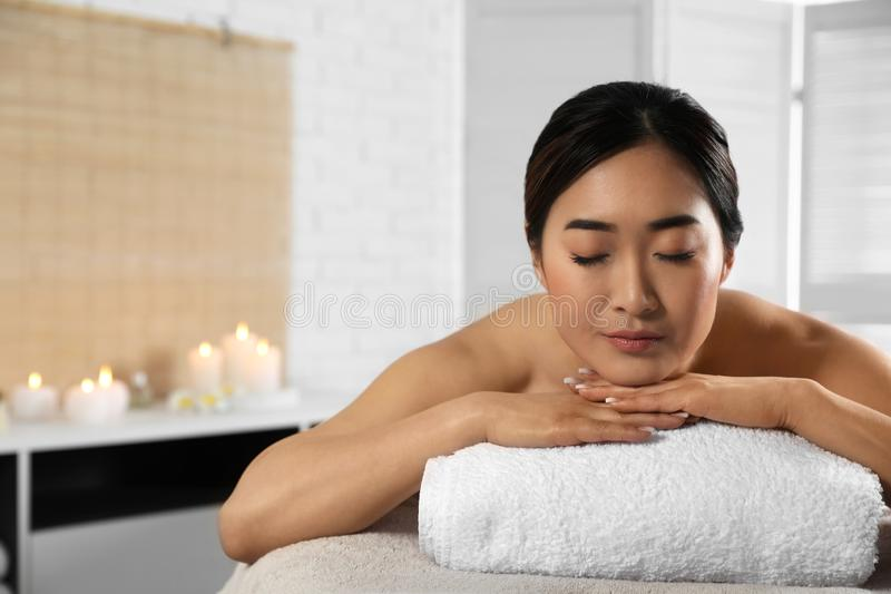 Mujer asiática hermosa que miente en la tabla del masaje en salón del balneario imágenes de archivo libres de regalías