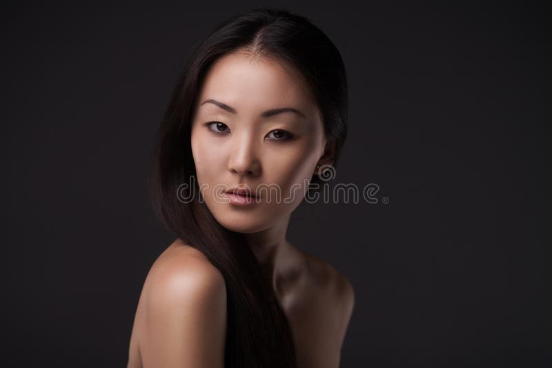 Mujer asiática hermosa que mira la cámara fotografía de archivo