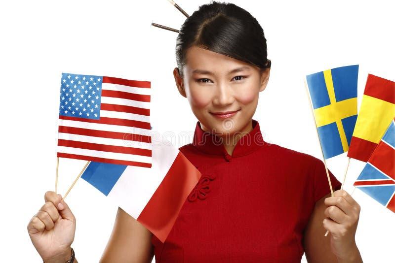 Mujer asiática hermosa que muestra banderas internacionales multicoloras foto de archivo libre de regalías