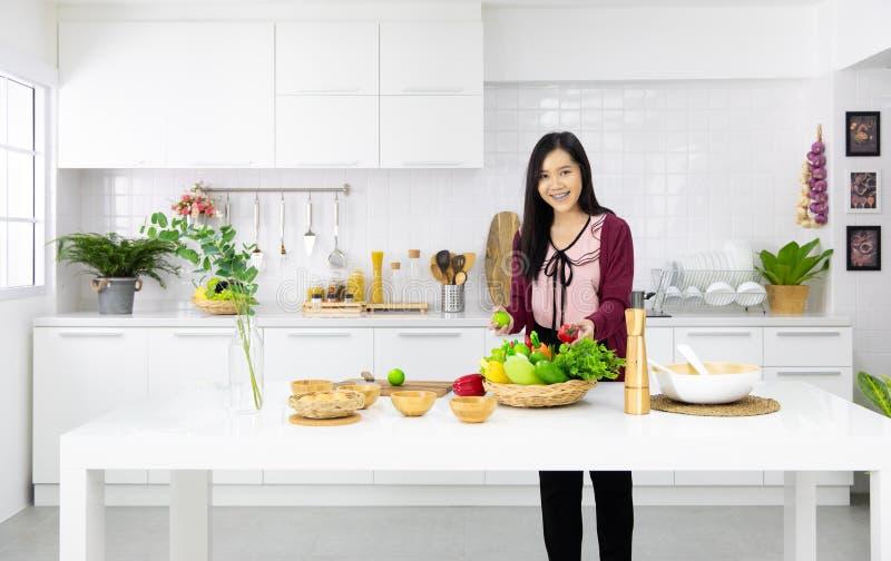 Mujer asiática hermosa que muestra su nuevos decoración de la cocina y pla foto de archivo libre de regalías