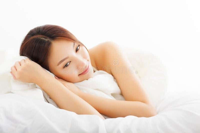 Mujer asiática hermosa que se relaja en la cama imagen de archivo