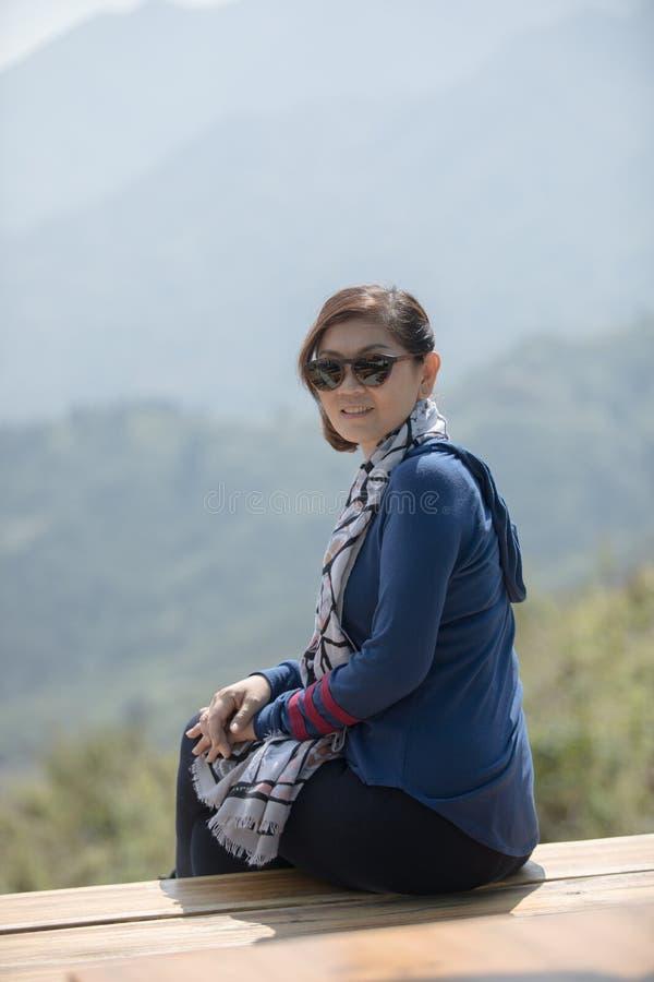 Mujer asiática hermosa que se sienta en la terraza de madera con smilin dentudo imagen de archivo