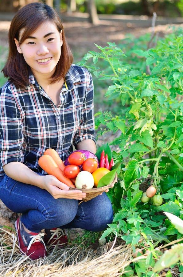 Mujer asiática hermosa que sostiene el cubo de las verduras frescas imagenes de archivo