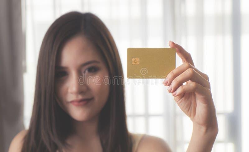 Mujer asiática hermosa que sostiene la tarjeta del crédito en blanco fotos de archivo