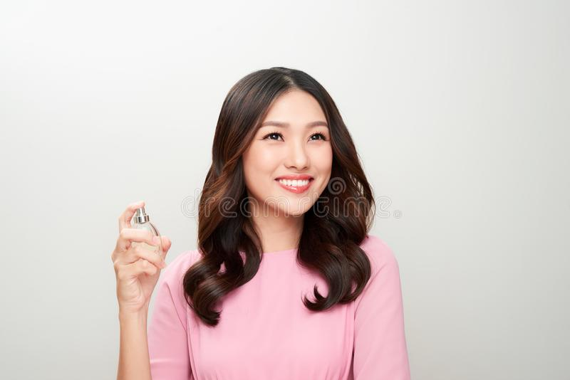 Mujer asiática hermosa que sostiene una botella de perfume y que la aplica imagen de archivo
