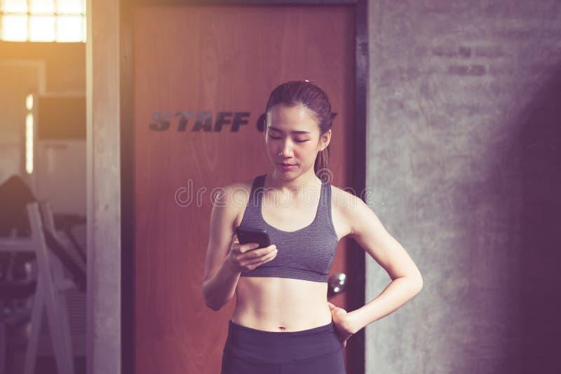 Mujer asiática hermosa que usa Internet con el teléfono elegante en el gimnasio, feliz deportivos y la sonrisa foto de archivo